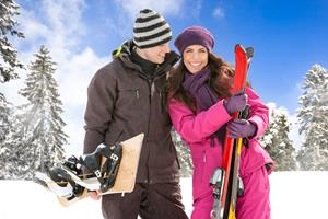 Couple standing on a snowy mountain in ski outfit