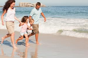 family running on a beach