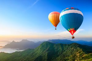 hot-air balloons flying over the mountain
