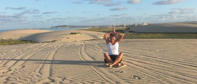 A woman doing yoga on the beach while on her travels
