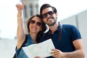 Portrait of young tourist couple use their map and pointing where they want to go.