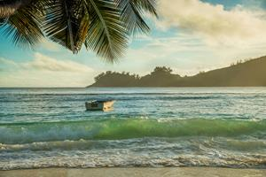 Tropical beach Baie Lazare with boat at sunset, Mahe island, Seychelles - vacation background
