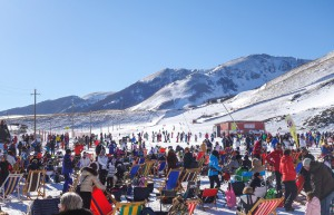 Roccaraso, Italiy - January 4, 2015: People relaxating at the outdoor lounge on winter sport resort in Roccaraso ski resort of south central Italy. Group of skiers sitting in the snow relaxing talking.