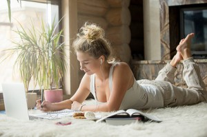 smiling young woman lying on white carpet studying with books and laptop in modern living room
