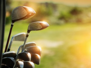 Golf clubs drivers with sun reflecting on them over green field background