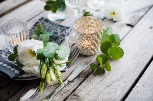 Table with white flowers, candles and glasses on old vintage wooden table.