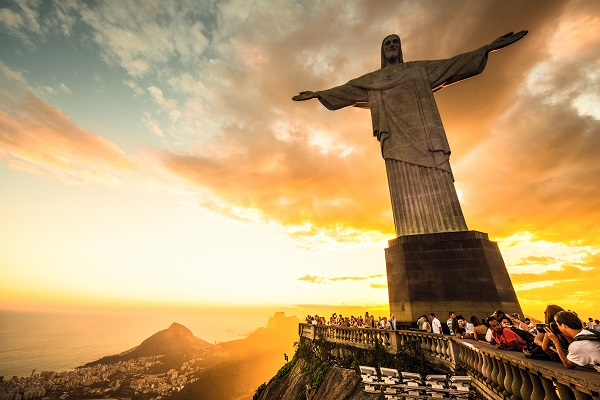 statue of christ the redeemer in brazil, with tourists surrounding it to take pictures in the sunset