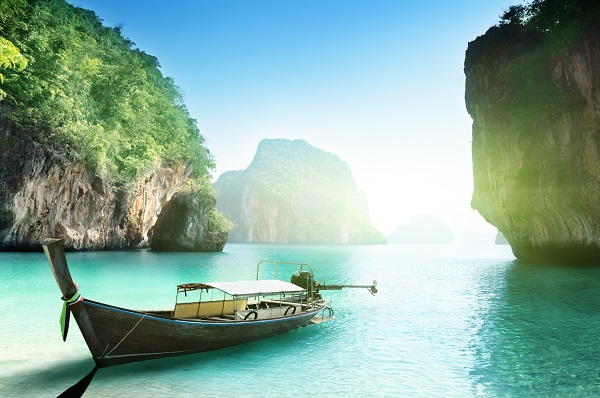 long-tail boat resting on clear blue sea between two cliffs on a small island in thailand