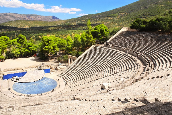 ancient theatre in greece looking down towards a stage, with mountains in sunshine in the background