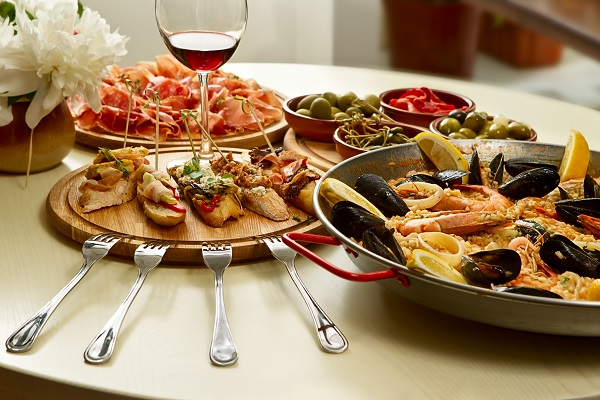 seafood served on a dinner table with a glass of wine and white flowers with four silver forks