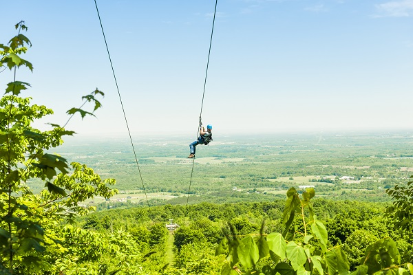 person ziplining down a zipwire over a green forest