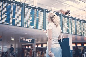 Young blonde woman with handbag, phone and tickets in her hands checking flight timetable in airport