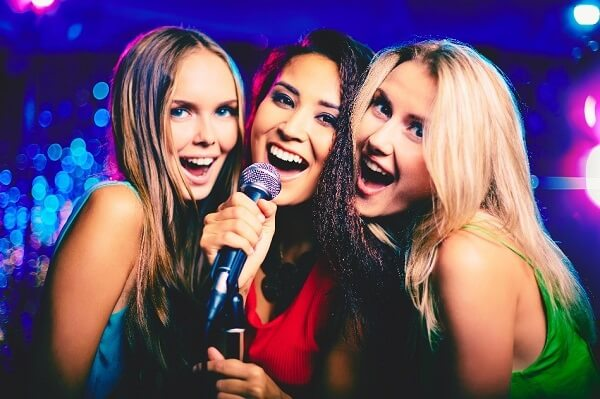 Three women singing Karaoke