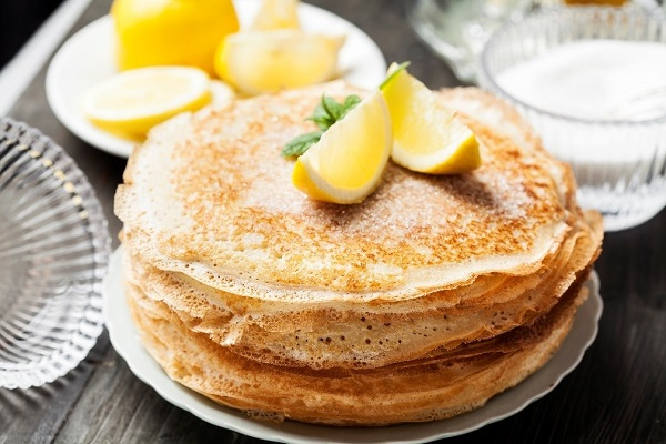 stacked pancakes topped with two lemon wedges