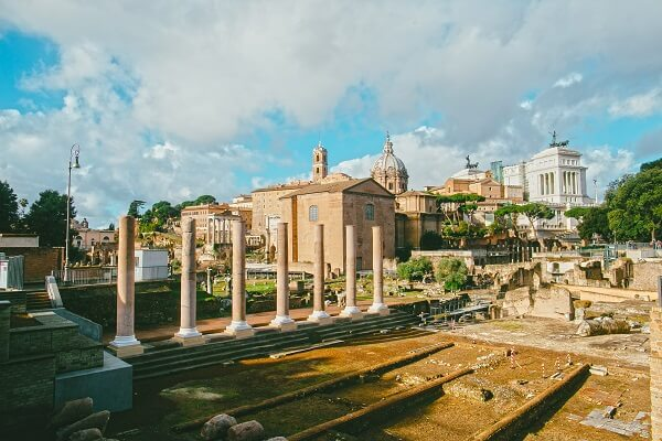 pillars and buildings in an ancient roman city with cloudy skies